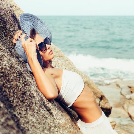 夏日当たりの良いファッションは海の海岸に一人で岩にポーズかなり若いの官能的な女性の肖像画。アウトドア ライフ スタイルの肖像画 写真素材