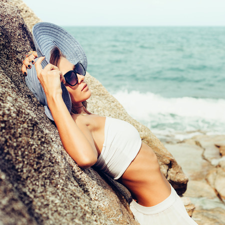 Summer sunny fashion portrait of pretty young sensual woman posing on the rocks alone on the ocean seashore. Outdoors lifestyle portrait Standard-Bild