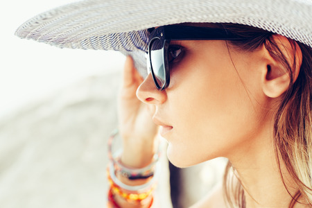 Face of young summer sexy woman wearing hat  and sunglasses. Outdoors lifestyle portrait