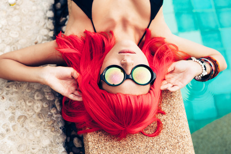Beautiful woman with red wig hair in black bikini and sunglasses relaxing beside a swimming pool. Outdoors lifestyle portrait