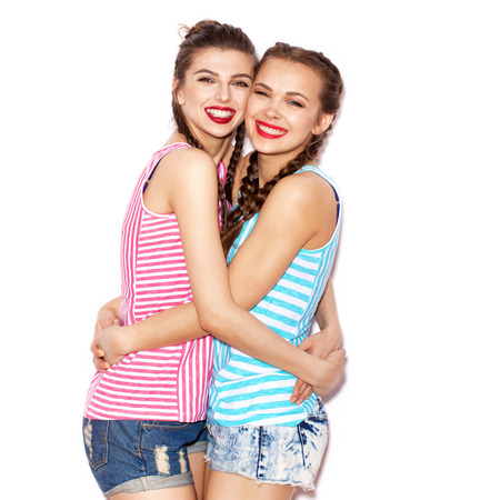 not painted: Two fashion laughing painted girl friends hugging and having fun. White background not isolated Stock Photo