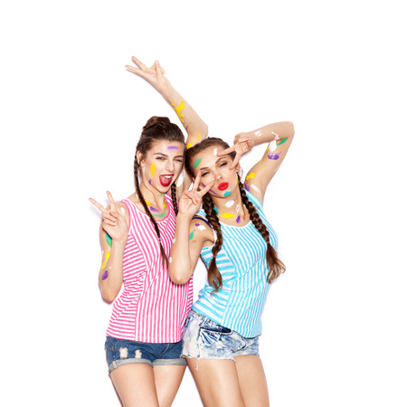 Two smiling painted girl friends fooled and having fun. White background not isolated