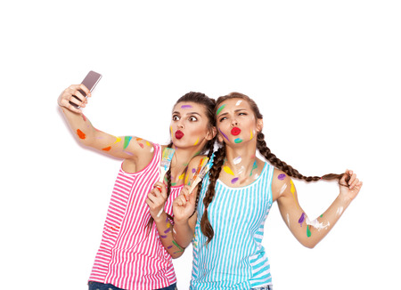 not painted: Painted girl friends having fun. Women with paintbrush taking selfie. White background not isolated