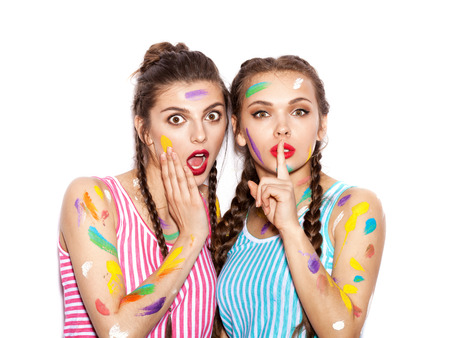Two surprised Smeared in paint girl friends looking at the camera. Women looking at camera and making a hush gesture. White background not isolated