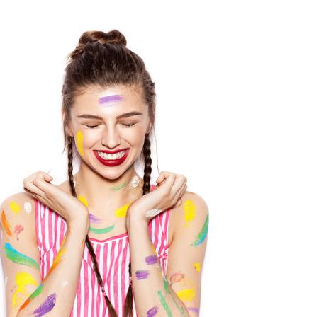 models posing: Joven alegre chica sucia en la pintura que se divierten. Mujer sonriente con maquillaje brillante y peinado con trenzas. Fondo blanco no aislados