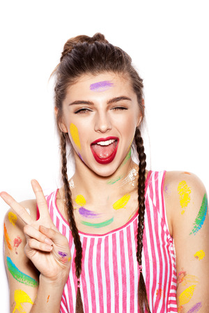 surprise party: Young cheerful soiled in paint girl having fun. Smiling Woman with bright makeup and hairstyle with pigtails. White background not isolated