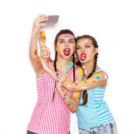 gente loca: La pintura en el rostro de los amigos de muchacha bonitos que se divierten. Mujeres con pincel Teniendo Autorretrato con su tel�fono. Fondo blanco no aislados
