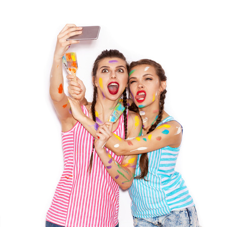 Paint on the face of pretty girl friends having fun. Women with paintbrush  Taking Self Portrait with Their Phone. White background not isolated