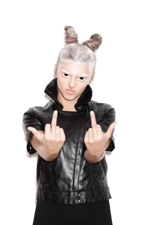 evil woman: A scary evil woman with black eyes showing middle finger for a fear or Halloween concept. Beauty girl with bright makeup hairstyle with horns in a black jacket having fun. Not isolated on a white background Stock Photo