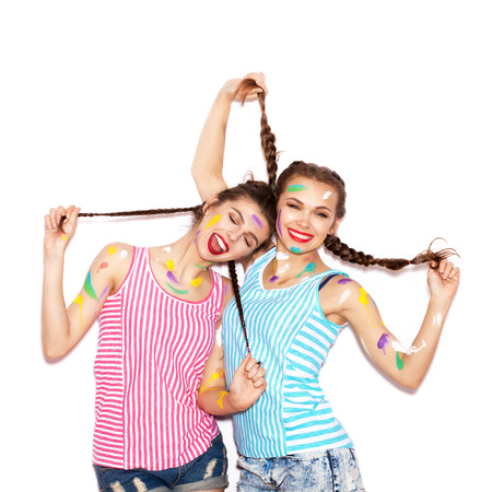 Two lovely girl friends hugging and having fun. Women smeared in paint. White background not isolated
