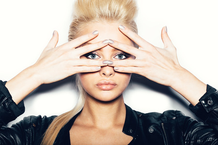 Stylish fashion blonde sexy young woman covered her face with her hand. Beauty girl in black clothes with bright makeup and hairstyle . White background, not isolated 스톡 콘텐츠