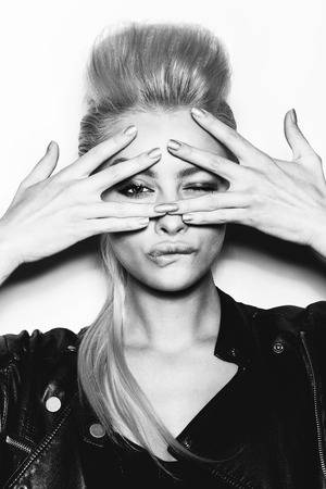 Stylish fashion blonde sexy young woman covered her face with her hand. Beauty girl in black clothes with bright makeup and hairstyle . Black and white toned. White background, not isolated
