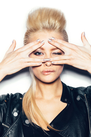 Stylish fashion blonde sexy young woman covered her face with her hand. Beauty girl in black clothes with bright makeup and hairstyle winking and flirting. White background, not isolated