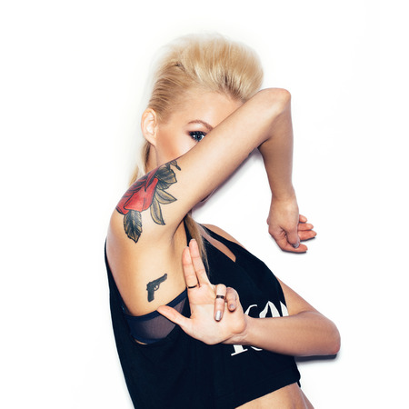 Stylish fashion blonde girl with tattoo in a black t-shirt gun shows.  White background, not isolated