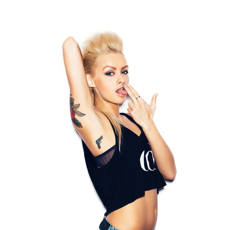 Stylish fashion blonde sexy young woman with tattoo in a black t-shirt gun shows.  White background, not isolated