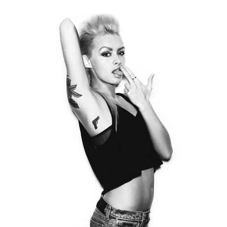 Stylish fashion blonde sexy young woman with tattoo in a black t-shirt gun shows. Black and white toned. White background, not isolated Фото со стока