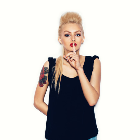 Blonde woman in a black dress flirting and looking at camera.  Girl making a hush gesture. White background, not isolated