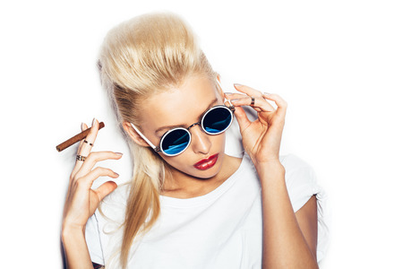 Blonde woman in sunglasses and white t-shirt smoking cigar.  White background, not isolated