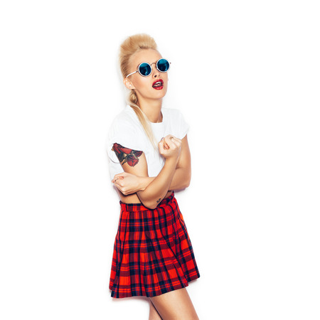 woman white shirt and plaid skirt  showing rude gesture. Beauty girl in sunglasses with bright and make-up hairstyle having fun. White background, not isolated