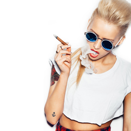 Sexy woman in sunglasses and white t-shirt blowing smoke from a cigar. Swag style girl. White background, not isolated Standard-Bild