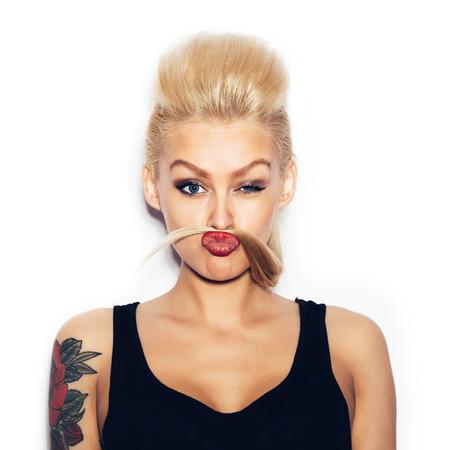 tatouage sexy: Mode butin sexy jeune femme blonde amuser et regardant la caméra. Fille avec maquillage lumineux montrant une moustache de la chevelure. Fond blanc, pas isolé Banque d'images