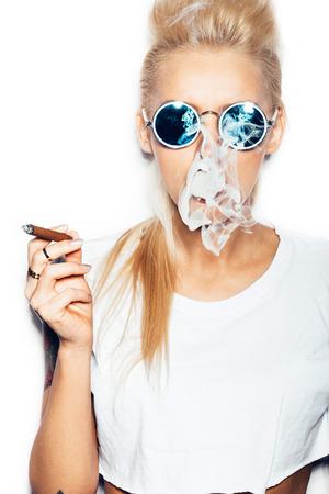 femme blonde: Femme blonde sexy en lunettes de soleil et t-shirt blanc soufflant la fumée d'un cigare. Swag fille de style avec lumineux maquillage et la coiffure. Fond blanc, pas isolé Banque d'images