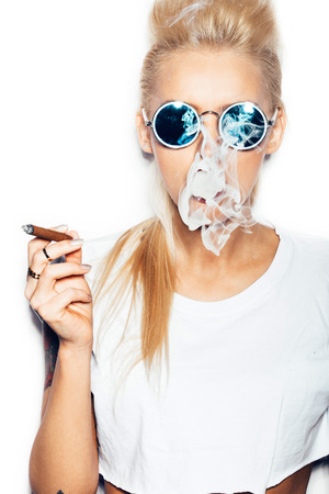 Sexy blonde woman in sunglasses and white t-shirt blowing smoke from a cigar. Swag style girl with bright make-up and hairstyle. White background, not isolated