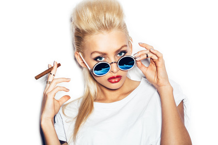Blonde girl in sunglasses and white t-shirt smoking cigar.  White background, not isolated Stockfoto