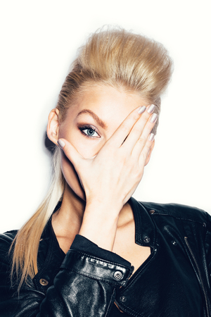 posing: Stylish fashionable blonde woman in black clothes covered her face with her hand. White background, not isolated Stock Photo