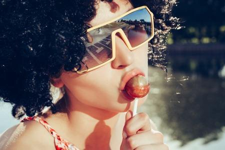 yummy: girl with black wig hair sucks lollipop. Outdoors lifestyle