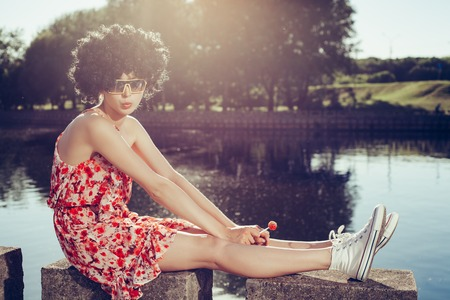sucks: girl with black wig hair sucks lollipop. Outdoors lifestyle