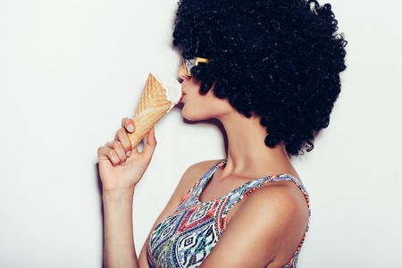 woman ice cream: Sexy young woman eating ice cream over White background not isolated