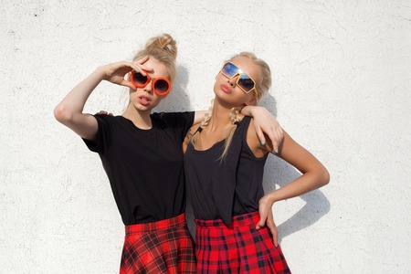 portrait of two pretty hipster blonde sisters  wearing plaid skirt and black T-shirt Stockfoto