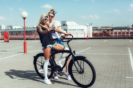 camera girl: two young women taking selfie with mobile phone on black bike. Outdoor lifestyle portrait Stock Photo