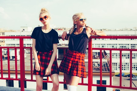 portrait of two pretty hipster blonde sisters  wearing plaid skirt and black T-shirt against  urban city. Stok Fotoğraf