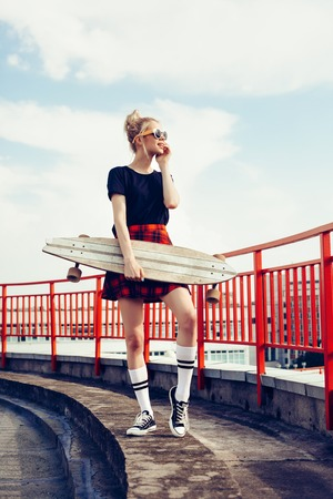 trend: Portrait of pretty young seductive woman posing with longboard desk outdoors lifestyle Stock Photo