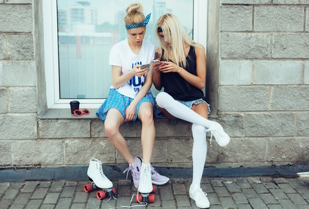 roller: filtered photo of two friends using their smart phones outdoors lifestyle Stock Photo