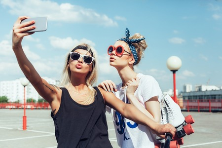 fashion sunglasses: two young women taking selfie with mobile phone Stock Photo