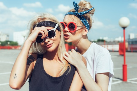 Two beautiful happy girls in sunglasses looking into the distance on the urban background