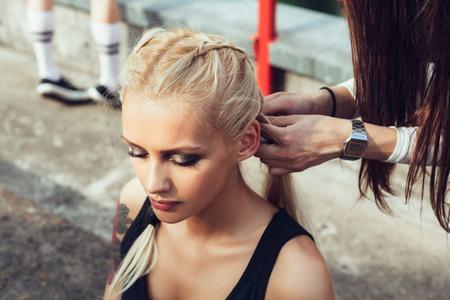 cornrows: Young female friends having fun outdoors. Girl braids cornrows her girlfriend
