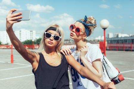 携帯電話で selfie を取って二人の若い女性 写真素材