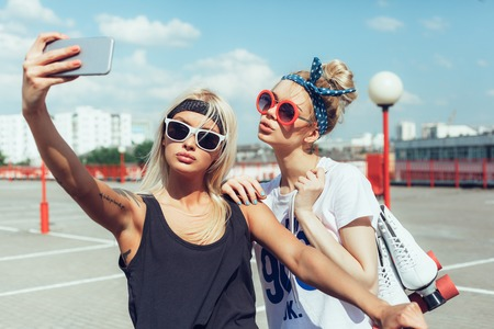 two young women taking selfie with mobile phone 스톡 콘텐츠
