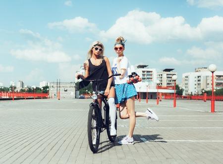 mujeres fashion: Retrato de la moda al aire libre de las mujeres jóvenes atractivas con bicicletas y patines de ruedas