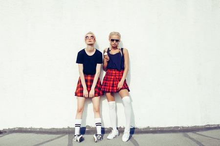 portrait of two pretty hipster blonde sisters  wearing plaid skirt and black T-shirt Фото со стока