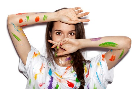 happy smiling: Young cheerful soiled in paint girl having fun covering her face with her hands on White background