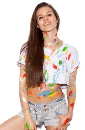 pelo largo: Joven alegre chica sucia en la pintura con el pelo largo que se divierten