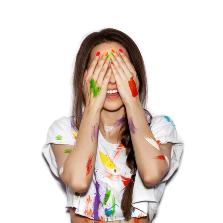 face paint: Young cheerful soiled in paint girl covering her face with her hands on White background Stock Photo