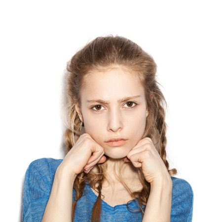contorted: Young girl with two hands in fists, face contorted in anger and frustration.   Stock Photo