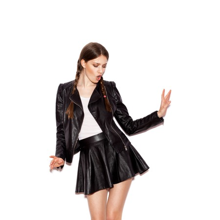 Girl with pigtails in black leather jacket. Woman dancing. White background not isolated
