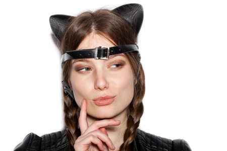 naughty woman: Young serious woman with leather cat ears. White background not isolated. Indoor lifestyle portrait of girl Stock Photo